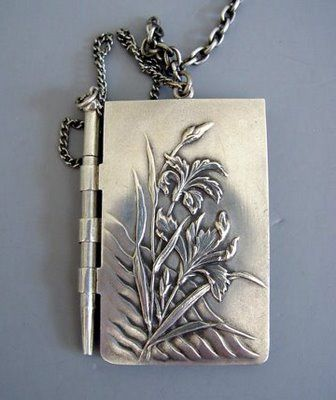 A silver notebook and pencil that was suspended from a chatelaine