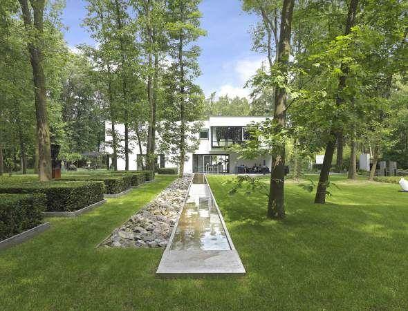 puur tuinarchitectuur en realisaties modern wit huis, groen gras en hoge bomen