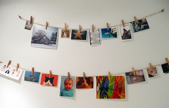 clothes pin and photos.  want to try, but would have to use something other than push pins so as not to damage walls