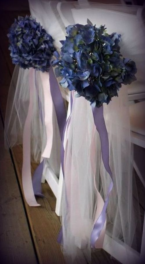 chairs with chair covers and sprays of blue flowers and purple ribbons hanging from the back of them !!!