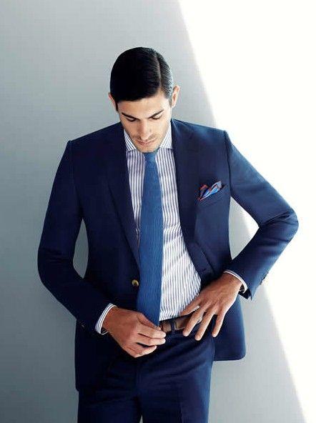 Costume bleu marine, cravate bleue sur chemise rayée bleue.
