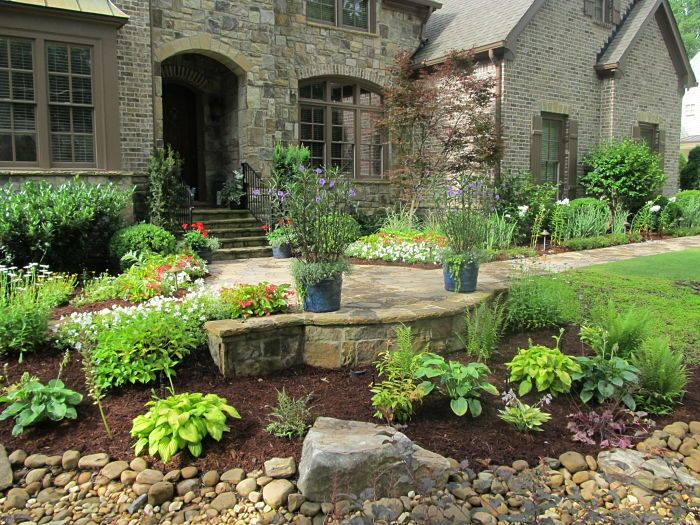 A paver walkway and patio, with a stone retaining wall and container gardens