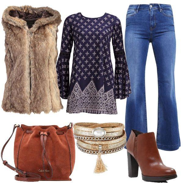 Jeans a zampa e maglia con maniche larghe a fantasia geometrica. Smanicato in eco-pelliccia con cappuccio, bracciale con cinturino dorato. Stivaletto e borsa a tracolla in pelle brown.