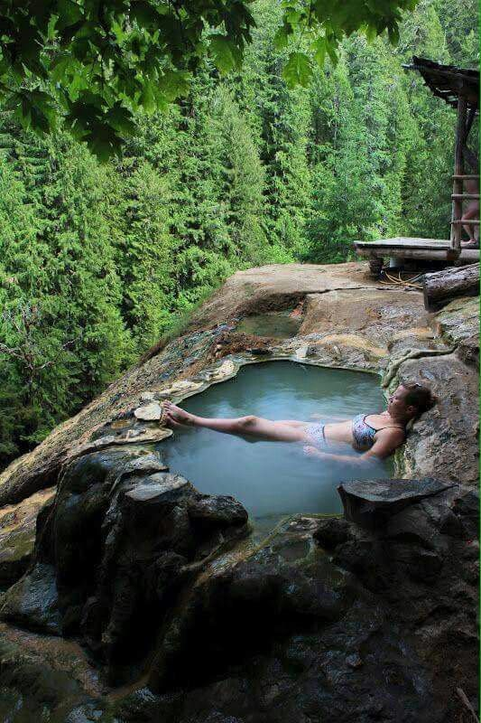 """In Roseburg, OR The Umpqua Hot Springs Trail is a short 0.3 mile hike to the springs. A """"tub"""" is hewn out of the travertine deposits surrounding the springs. The springs, at a temperature of 108 degrees, is located on a bare rock face 150 feet above the North Umpqua River. From the tub, there is a view of Surprise Falls across the river."""