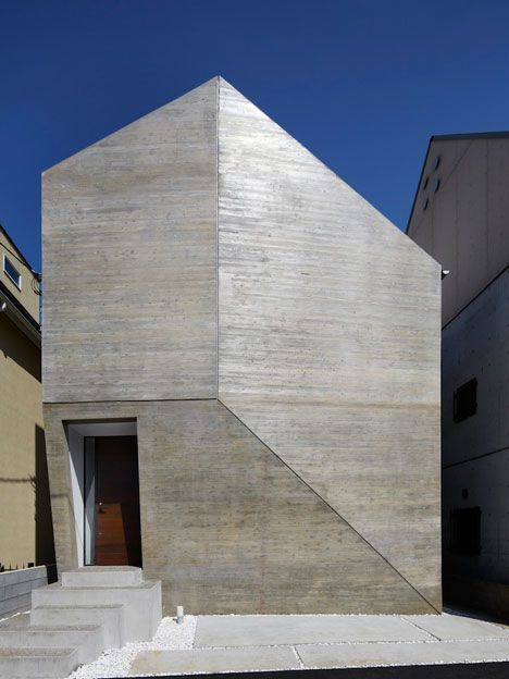 A doorway is the only opening in the faceted concrete facade of this family residence in Tokyo by architecture studio MDS.
