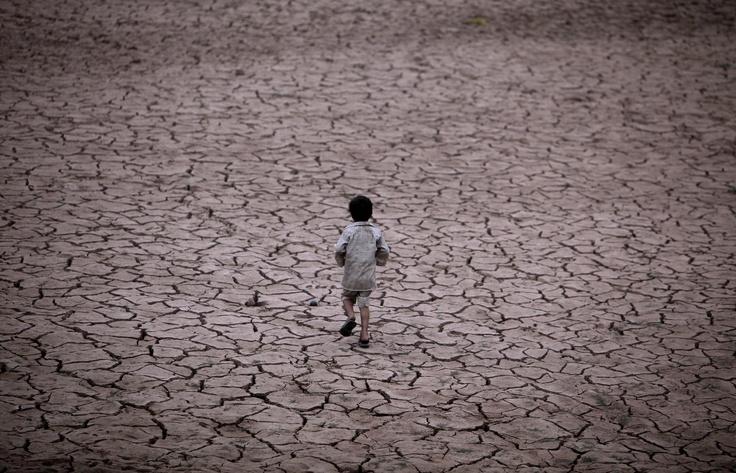 Un niño pakistaní camina de regreso a su casa por lo que antes era un río a las afueras de Islamabad, Pakistán. / AP
