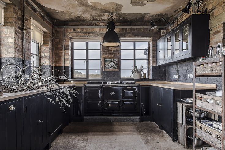 HMS Owl, a restored Scottish WWII control tower, has a new British Standard kitchen with off-black, charcoal cabinets set off by its original brick walls.