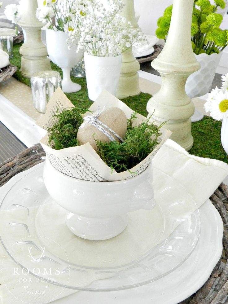 All white with green accents, egg wrapped with twine, book papers under grass or moss