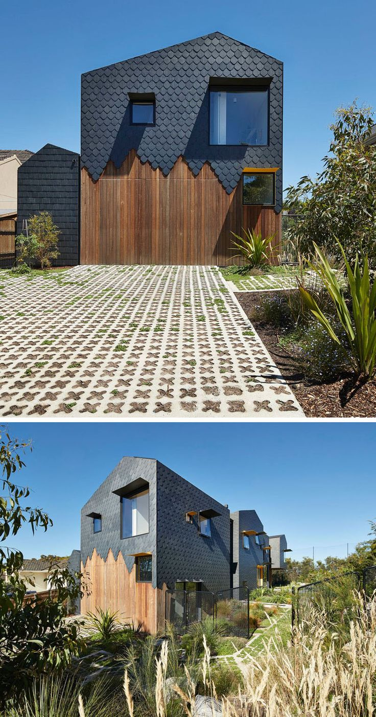 Covering the exterior of this modern house are dark grey slate tiles in a couple of different patterns, with some sections having a staggered finish to show the wood underneath, especially at the side of the home where the garage is located.