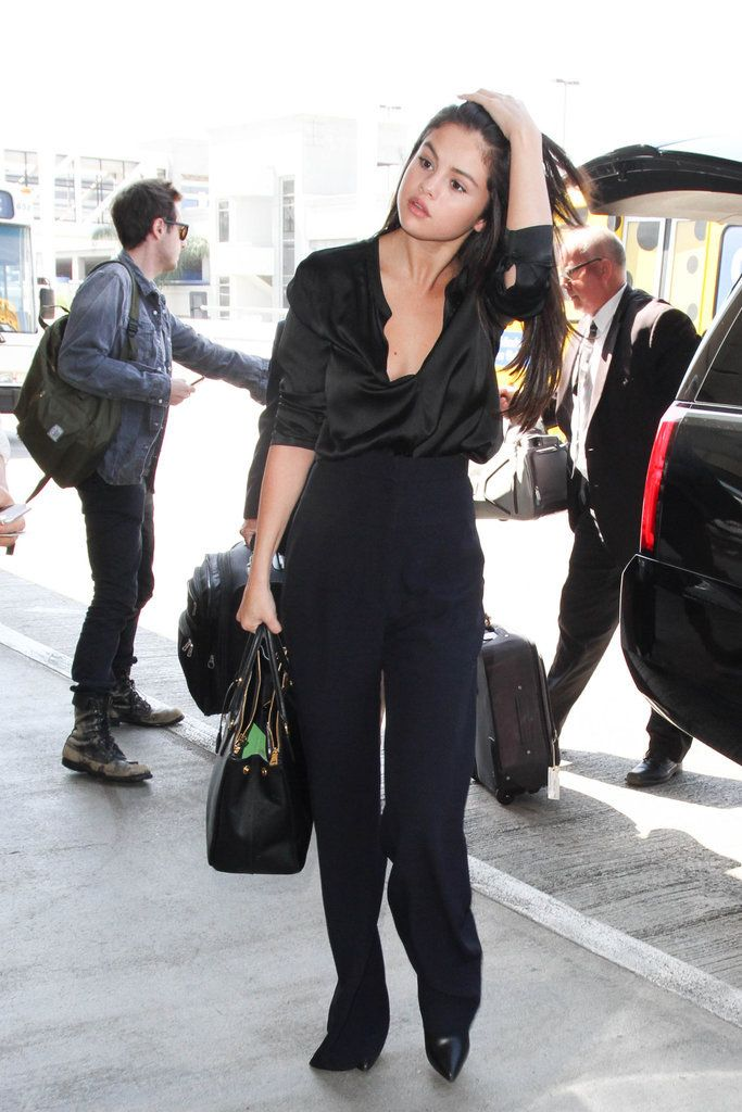 Selena styled her silk, open-front blouse with a pair of wide-leg high-waisted trousers. Her leather pointed-toe booties peeked out from beneath her pants as she walked confidently into LAX.
