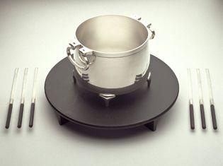 Fondueset, Silber und Gusseisen, mit 6 Fonduegabeln aus Silber und Ebenholz und Messingspiritusbrenner, Maße: DxH 45x25 cm, Volumen: 4,0 ltr., Gewicht 14 kg