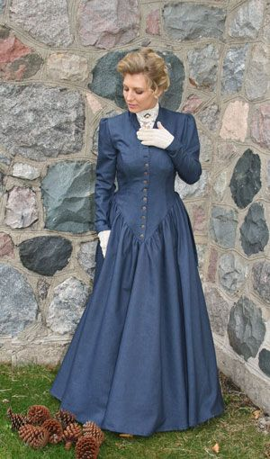 "Price: $159.95  Who would have thought that denim could be this elegant? Limited supply left! This Victorian styled dress is made up in 100% cotton denim. We love the little buttons that close the front, and the flirty bustle effect in the back. The fitted bodice features a high collar, and long sleeves with a little extra ""head room"" at the top. A deep ""V"" at the front of the bodice slims the waistline, and the three-gored gathered skirt can be made up in boot length or floor length."