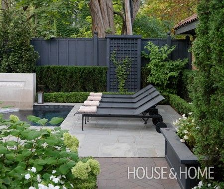 Dark grey timber work with lighter grey paving & surrounded by lush green plants with white flowers