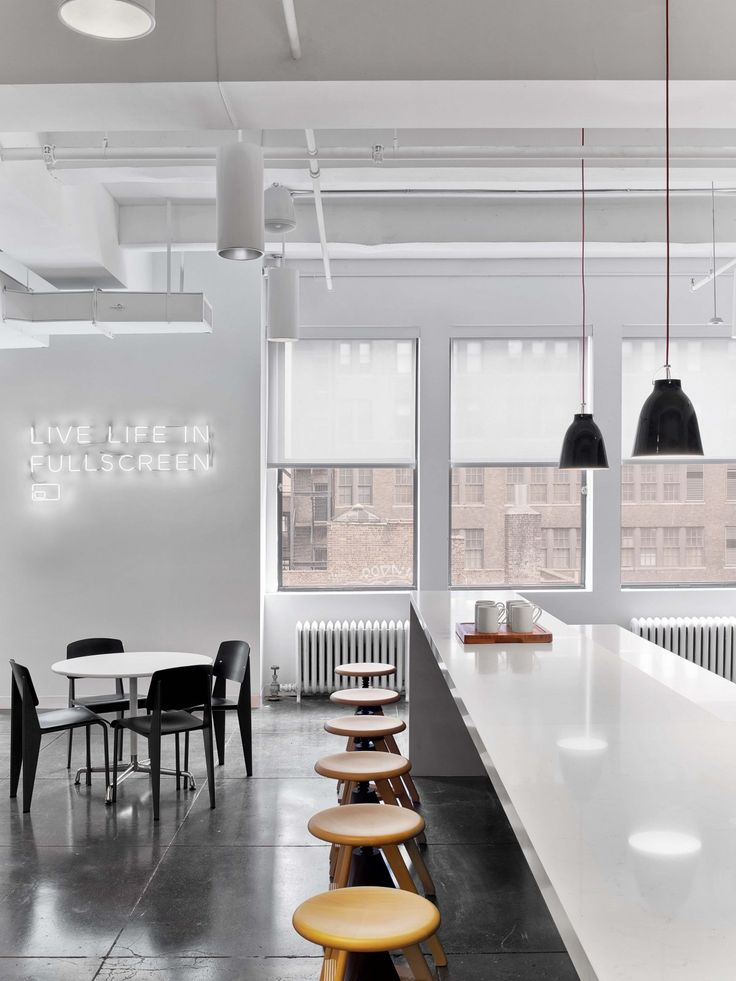 Fullscreen Offices – New York City. Media company. Breakout. Collabroation. T point. Kitchen. Breakfast bar. TOuchdown. Bar stools. Neon sign. Exposed ceiling.