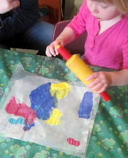 "Art - this simple painting activity - spoon or squeeze paint onto wax paper, place another piece of wax paper on top, allow children to roll a rolling pin over the ""sandwiched"" paper - can attract children that aren't typically attracted to art because of items not typically used in art"
