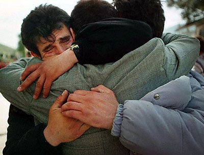 Young Kosovar men from Prizren weep and embrace after crossing the Albanian border at the Morina checkpoint. Carol Guzy.