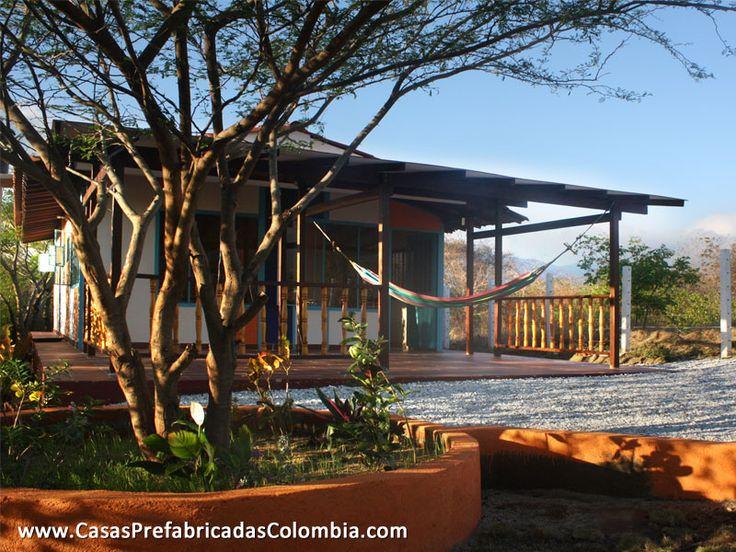 Casa de un nivel en teja de barro, puertas y ventanas metálicas, cuenta con un porche frontal, barandas en madera.