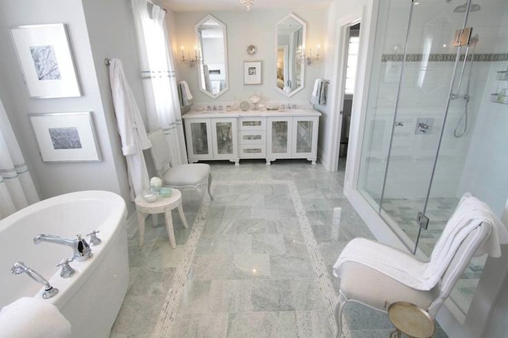 Huge marble ensuite bathroom with light gray walls paint color, antique mirror double bathroom vanity cabinets, white mirrors, marble tiles floor with mosaic marble inset tiles, freestanding oval tub and frameless glass shower.