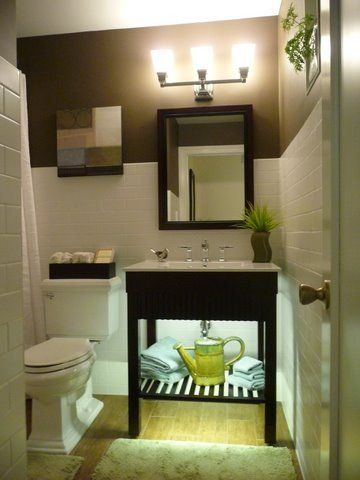 Small bathroom made to look larger. Undercabinet lighting for night light and ambience. White matte subway wall tile, wood flloor tile, contrasting paint – Benjamine Moore Brown Horse – to make the white tile