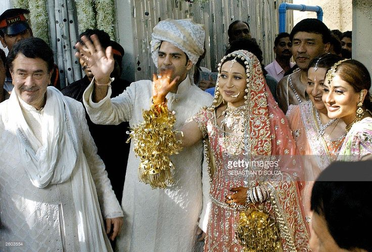 Indian film actress Karishma Kapoor (2-L)and her new husband Sanjay Kapoor (3-L) wave to the waiting as the father of the bride Randrir Kapoor (L), her sister Kareena (R) and mother Babita (2-R) look on in Bombay, 29 September 2003, following the couples wedding ceremony at the Kapoors ancestral home. The wedding of Krishma Kapoor to her childhood friend Sanjay Kapoor was attended by a large number of filmstars and celebrities. AFP PHOTO/Sebastian D