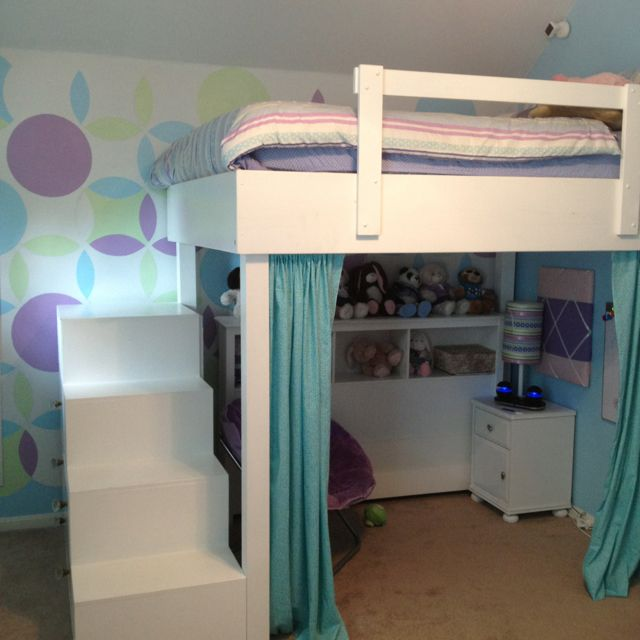 Loft bed with stair dresser and curtain reading nook underneath, also used as a stage for performances.