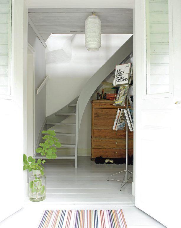 Gröna blad från trädgården i en glasvas ger atmosfär åt hallen med en vackert gråmålad trappa.