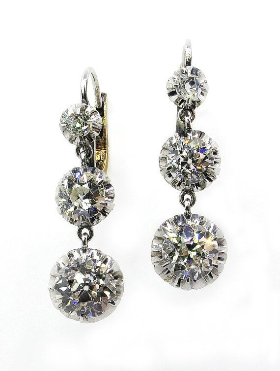 From our Authentic Antique Ear Pendants Collection! A Sexy pair of Victorian Diamond Drop Earrings in Platinum with 18K Yellow Gold Lever backs (tested). Consisting of 6 Graduated Mixed Old Mine and Old Euro Diamonds suspended in Buttercup Platinum settings. CIRCA 1890. The Larger Bottom Old Cut Diamonds are estimated to be Shy 1 carat EACH (0.99Ct), the entire outlines Diameter is 8.04mm, G-H Color VS Clarity. The middle section has an estimated 0.50ct Each Diamonds, the buttercups Diameter…