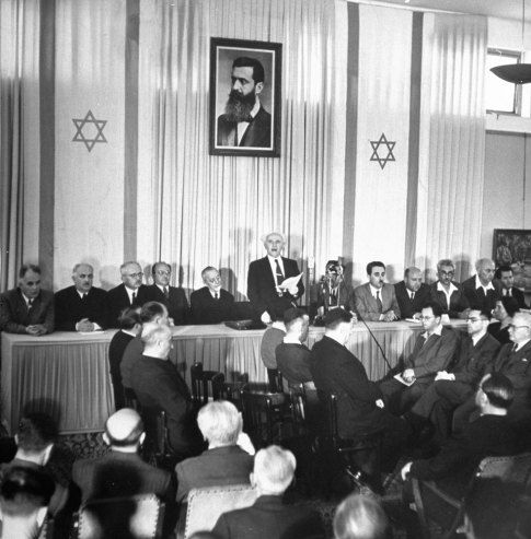 THE DAWN OF ISRAEL, 1948 - Proclamation of Nationhood is read by Israel's Prime Minister David Ben-Gurion. Around him are members of the provisional government, including Foreign Minister Moshe Shertok (third from right). Labor Minister Moshe Ben Tov (extreme right) wears sport shirt. Portrait above is of Theodor Herzl, Zionism's founder.