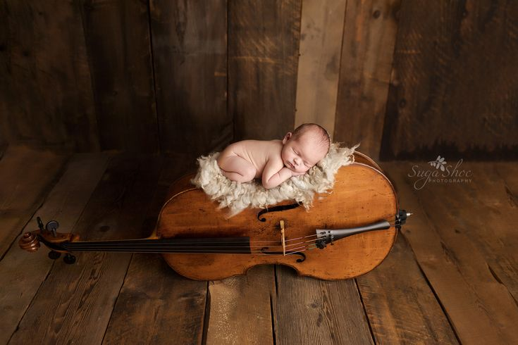 Newborn pose baby laying on cello sleeping