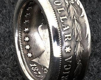 Esta doble cara plata moneda de anillo fue hecho a mano de un 90% nos Morgan Dollar moneda de plata, acuñadas en 1898. Está disponible en tamaños de 10-22 incluyendo tamaños medio. Este anillo de moneda 3D Lee Un dólar, Estados Unidos de América y IN GOD WE TRUST en el exterior y E PLURIBUS UNUM con fecha de menta en el interior. El ancho de banda es aproximadamente de 12 mm de ancho.  Información general: Todos nuestros anillos de plata de la moneda han redondeado los bordes para mayor…