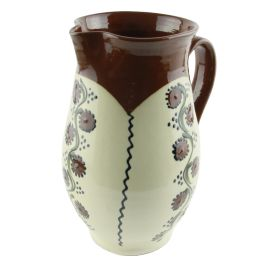 """This jug is carefully and painstakingly handmade from glazed Baia Mare ceramic and infused with the potter craftsmen' love and passion for their craft.The ivory white and brown paint enriched with leaf shaped motifs in shades of green, black and brown is signed by the craftsman Cornel Sitar, who hasn't stopped spinning the potter's wheel ever since 1962, when he was 13 years old. The product is customized with text """"Romania"""" on the lower side to certify its authenticity."""
