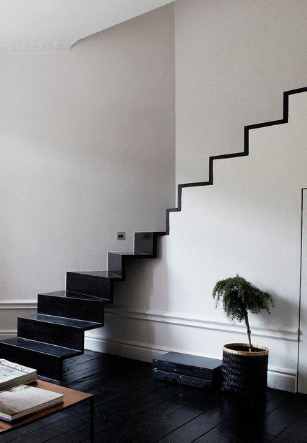 Apart effect voor het einde van een trap. Mooi decoratief zodat het makkelijk een onderdeel maakt van de leefruimte. Doordat de traden loskomen van de wand, lijkt het meer een los meubel en nodigt het ook uit om op te zitten.