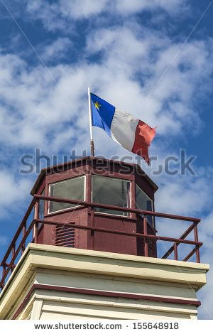 An Acadian flag on top of a lighthouse in rural Prince Edward Island, Canada