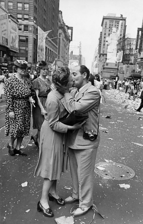 """NYC. In a photograph taken by LIFE colleague Bill Shrout, Alfred Eisenstaedt kisses an unidentified woman reporter in Times Square on VJ Day, August 14, 1945 — a powerful visual echo (in retrospect) of the now-iconic, era-defining """"sailor kissing a nurse"""" picture that Eisenstaedt himself shot that very same day. (William C. Shrout—Time & Life Pictures/Getty Images)"""