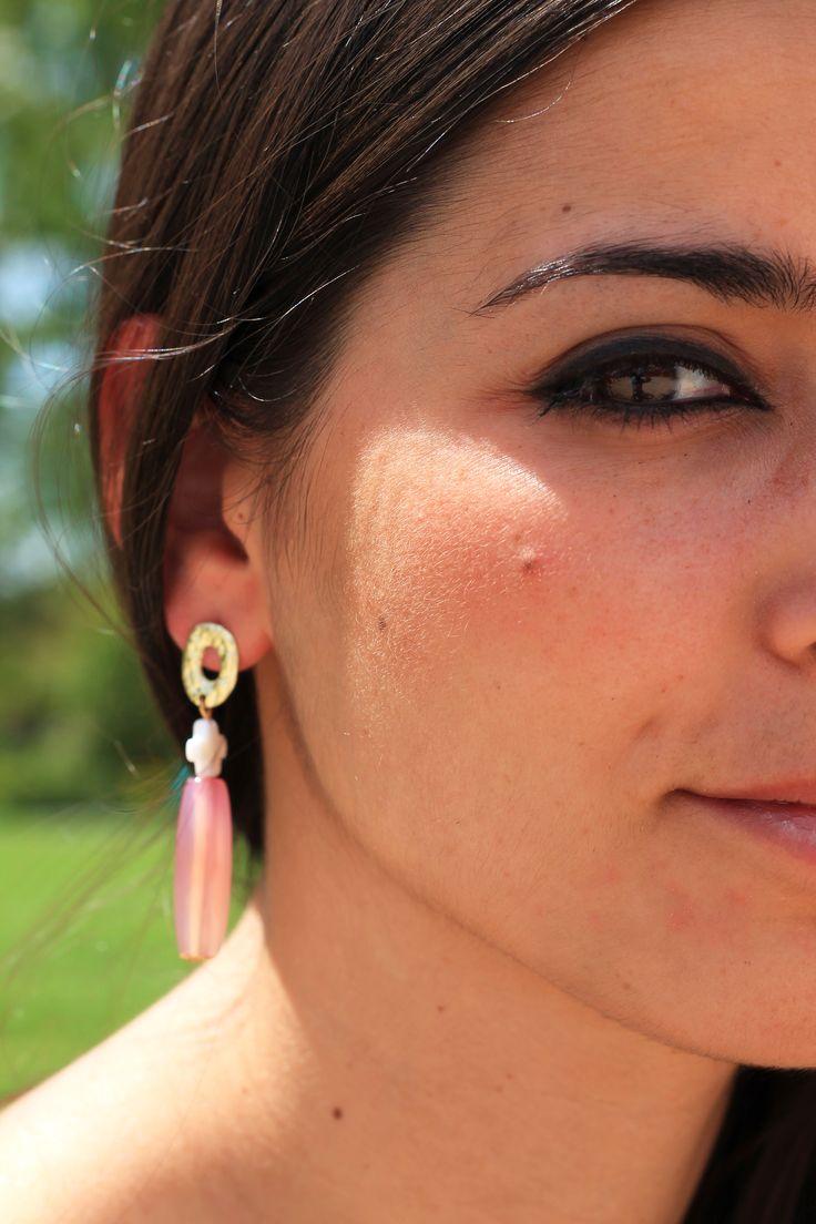 Preciosos pendientes compuestos por aro plano dorado del que cuelga una cruz de nácar y una piedra ágata rosa o ambar, según el modelo.