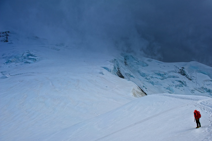 A lone alpine climber faces the storm approaching from the summit of Mont Blanc in Chamonix, France