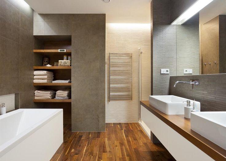 Do hlavní koupelny přechází dřevěná podlaha z předsíně. Nepřímým osvětlením lze podle potřeby měnit atmosféru a množství světla v koupelně.