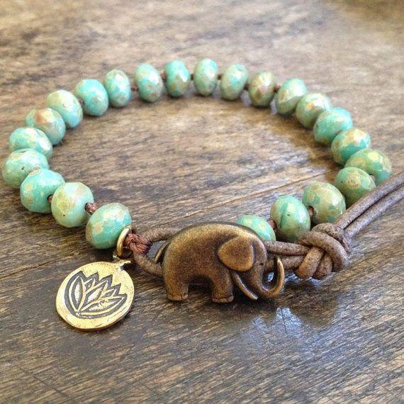Deze interne wrap armband beschikt over prachtige groen/turkoois picasso Tsjechische kralen hand geknoopt met donkere bruine nylon koord. De charme van een mooie bronzen lotus bungelt vanaf de lederen lus toe te voegen aan de schoonheid van dit stuk. Het strand sluit af met een schattig bronzen klaar olifant knop gesp en noodlijdende lederen lus. Prachtige kleuren!  Maatregelen 7,25 inch in lengte van centrum van lederen lus aan knop.  Ik gebruik alleen top kwaliteit kralen en lood/chroom…