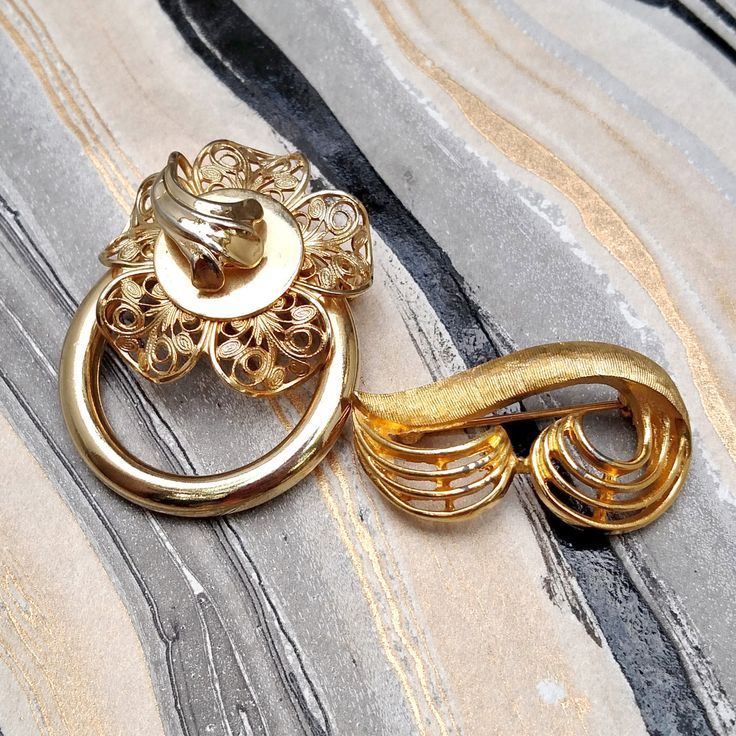 Two abstract gold toned Coro pieces roughly from around the 1970s. To the left there is an avant garde flower with filigree petals attached to a gold ring. To the right is a textured abstract wave like brooch. Both items are in good vintage condition. There is however slight chipping on the piece to the right. The luminescence of the item makes it hard to notice. Measurements and updated shipping to arrive shortly! If you would like a more definite shipping quote, please contact the shop…