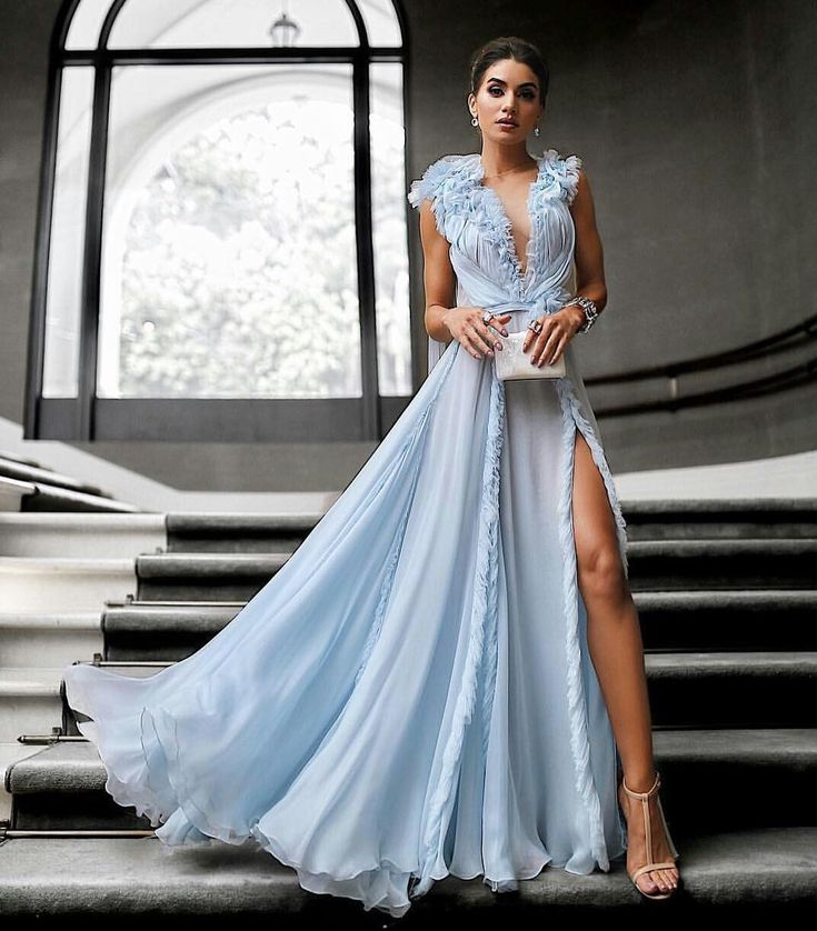 In a pale blue silk chiffon Haute Couture gown with pleated flowers and  cascading ruffles  <div class=