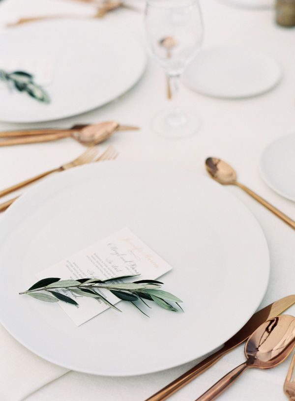 Keep the table as clear as possible, making creative (but sporadic) use of color. This beautiful tablescape is completely white except for the rose gold flatware and the little olive branch. The understated effect is simply breathtaking.