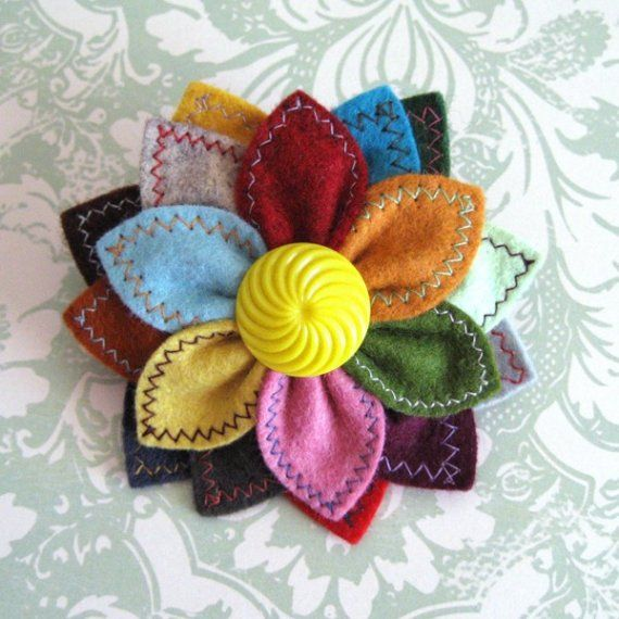 Prism Flower wool felt pin by pinksparrow on Etsy...love the vast array of colors of petals...would make a pretty ornament...Reminds me of a poinsettia
