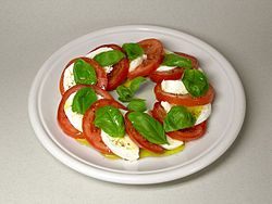 "Caprese salad (Italian: Insalata Caprese [insaˈlaːta kaˈpreːze], meaning ""Salad of Capri"") is a simple Italian salad, made of sliced fresh mozzarella (ideally Buffalo mozzarella), tomatoes, and green basil, seasoned with salt and olive oil. It is made to resemble the colors of the Italian flag: red, white, and green. In Italy, it is usually served as an antipasto (starter), not a contorno (side dish)."
