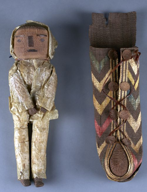 Tlingit Doll and Cradle, ca. 1900, Doll- seal intestine and raffia. Cradle - spruce root and split grass with false embroidery.