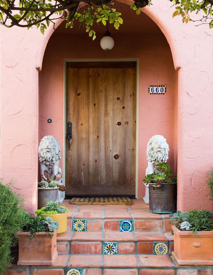 """Original handpainted terracotta tiles accent the home's welcoming covered entryway. """"You can definitely tell that it's an artist's house,"""" saysKarras."""
