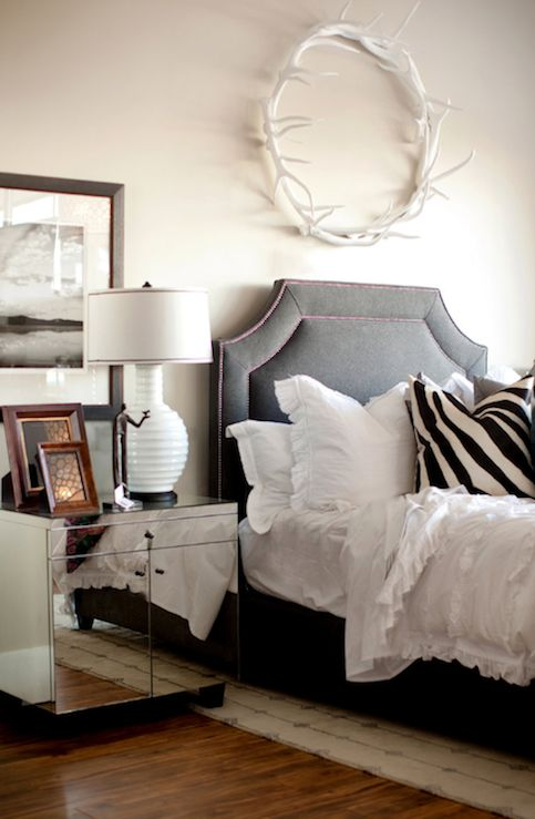 bedrooms - Oly Studio Antler Wreath Oly Studio Eva Bedside Table charcoal headboard bed red purple nailhead trim white ruffled bedding white black zebra pillows white ribbed lamp tan walls white horns round circle wall decor