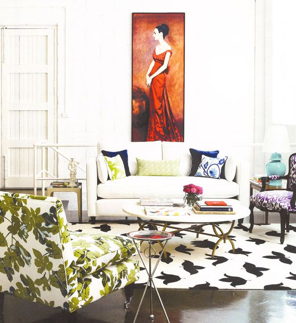 Ladylike eclectic living room with printed chair and painting.