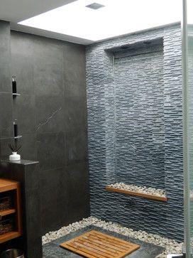 Bali Inspired Bathroom. The bathroom includes an 8ft skylight, waterfall, rain head shower, river rock, hidden shower drain, limestone, teak finishes, wall mounted toilet
