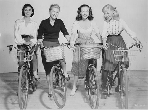 Jean Simmons, Joan Fontaine, Piper Laurie, and Sandra Dee on bicycles.