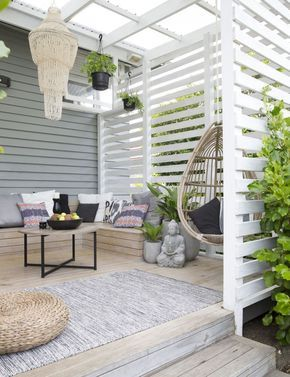 In this Auckland, New Zealand, beach home, a gracious porch has just enough space for an outdoor living room.   Photographer: Larnie Nicolson